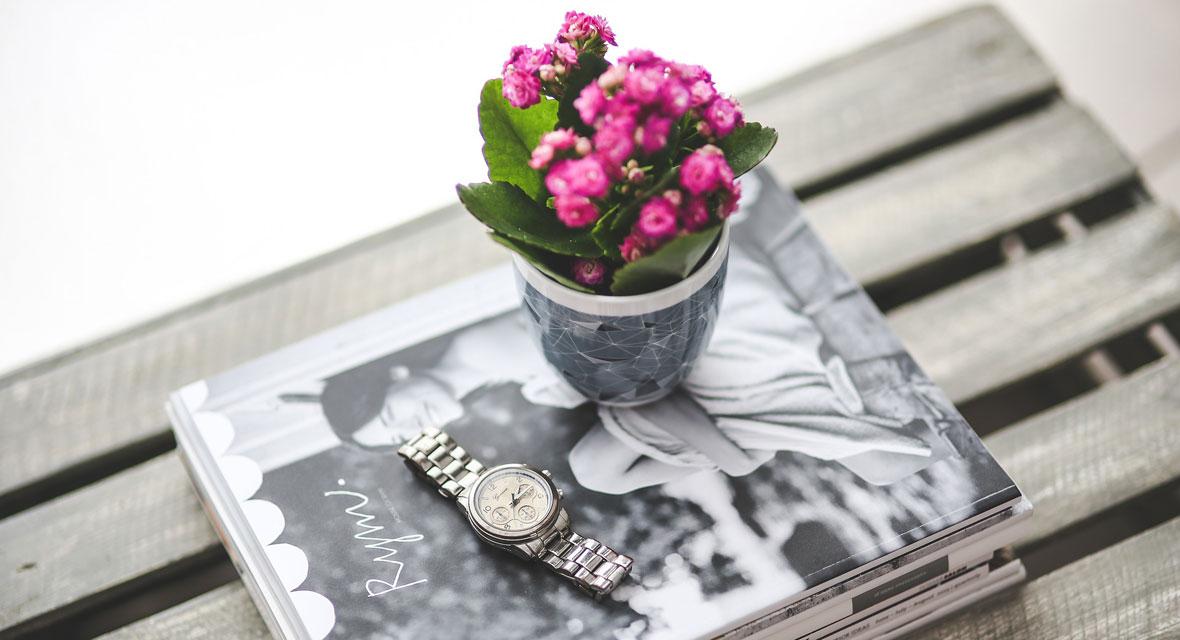 Uhr und Blume auf einem Tisch mit Magazinen