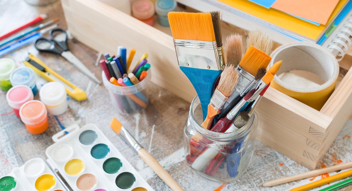 Bastelutensilien wie Pinsel und farben auf einem Tisch.