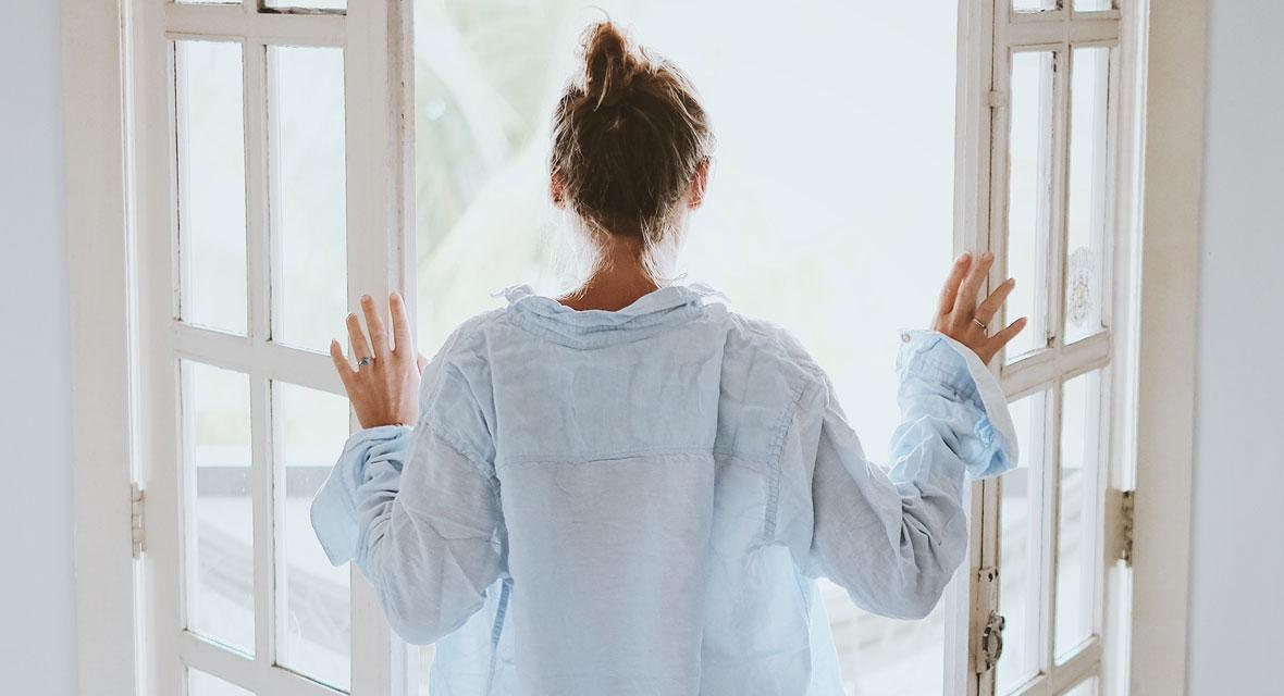 Frau im Hemd steht vor einem geöffnetem Fenster