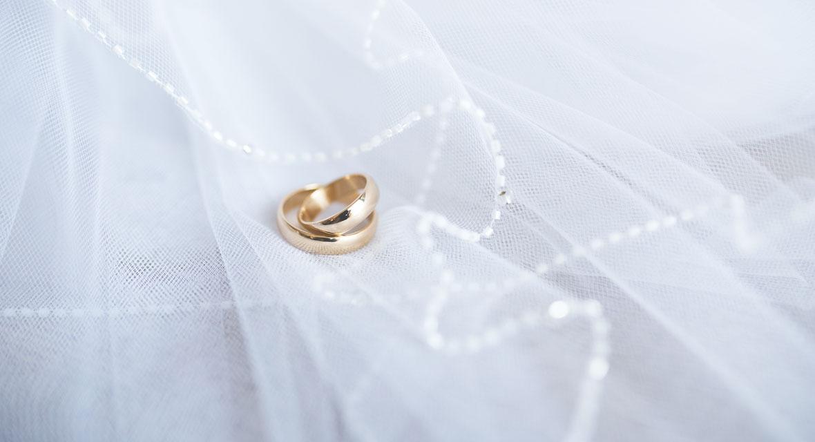 Goldene Eheringe auf einem Stück Tüll