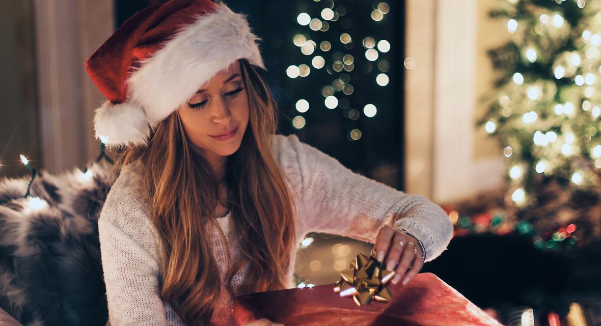 Frau öffnet Geschenk an Weihnachten.