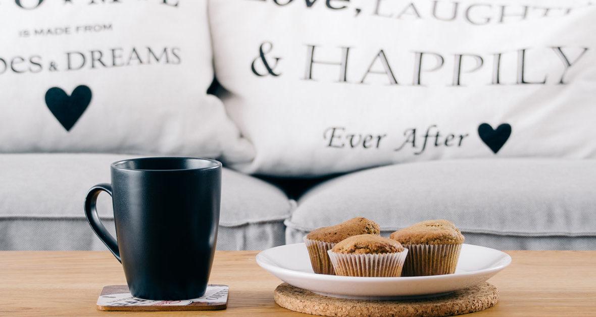 Kaffeetasse und Muffins stehen vor einer Couch mit Kissen