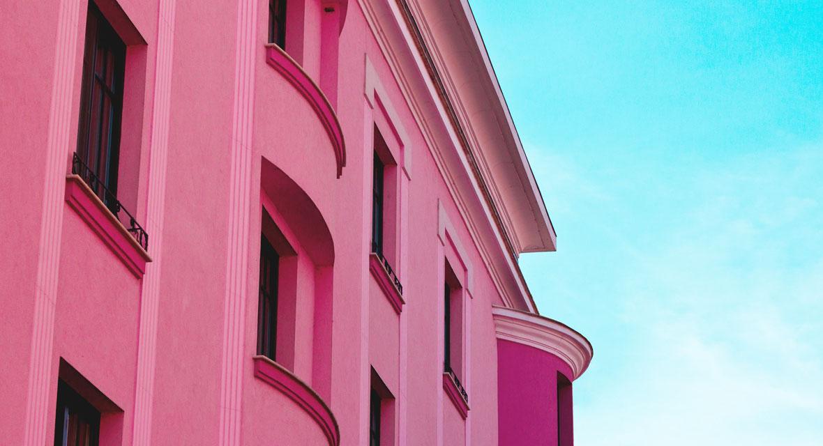Pinkfarbene Hauswand vor einem blauen Himmel