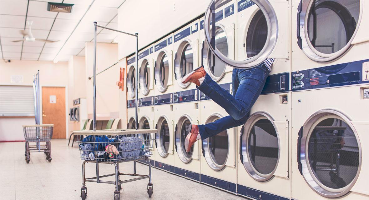 Eine Frau steckt in einer Waschmaschine in einem Waschsalon