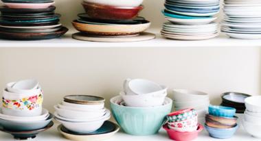 Teller, Schüsseln und mehr Geschirr steht in einem Regal