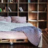 Ein Bett aus Paletten steht vor einem Regal