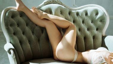 Eine Frau liegt in Unterwäsche auf dem Sofa