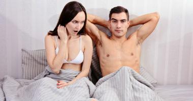 Ein Paar liegt zusammen im Bett.