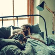 Ein Paar liegt mit seiner Morgenlatte im Bett.