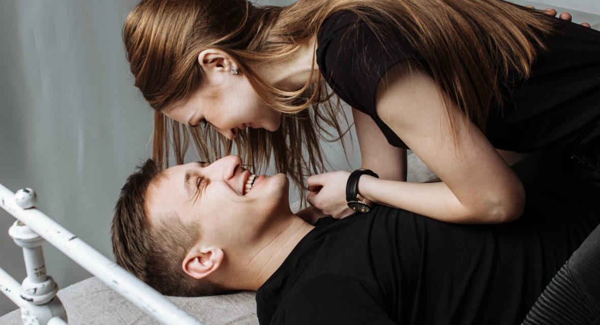 Ein Paar liegt mit angezogen im Bett