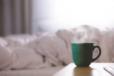 Eine dampfende Kaffeetasse steht vor dem Bett.
