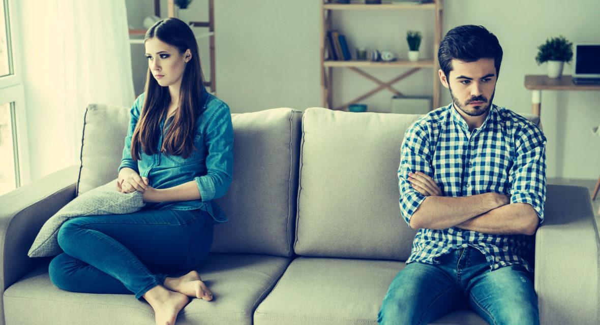 Ein Paar, das schweigend im Streit auf dem Sofa sitzt.