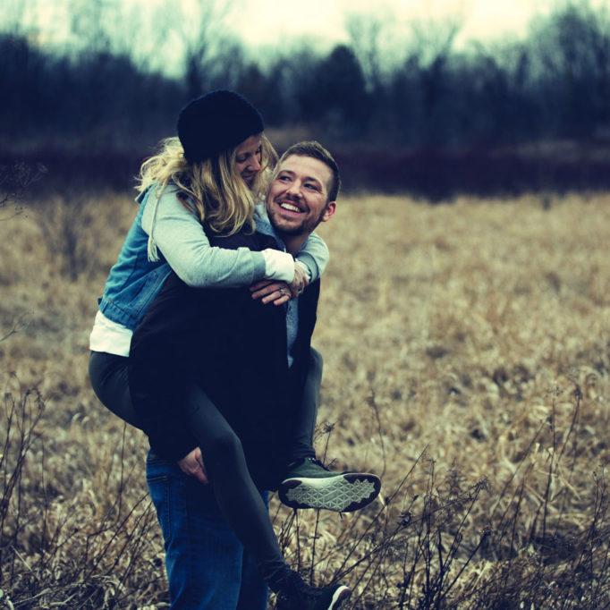 Ein Mann trägt eine Frau lachend auf seinem Rücken.