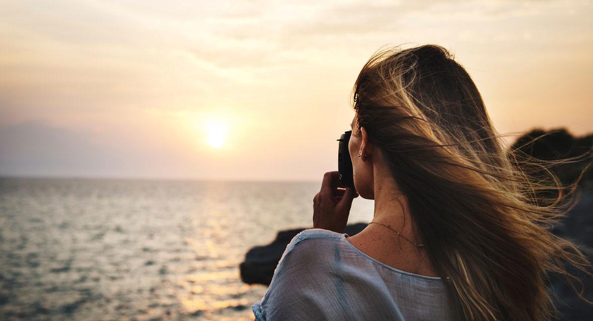 Frau fotografiert Sonnenuntergang