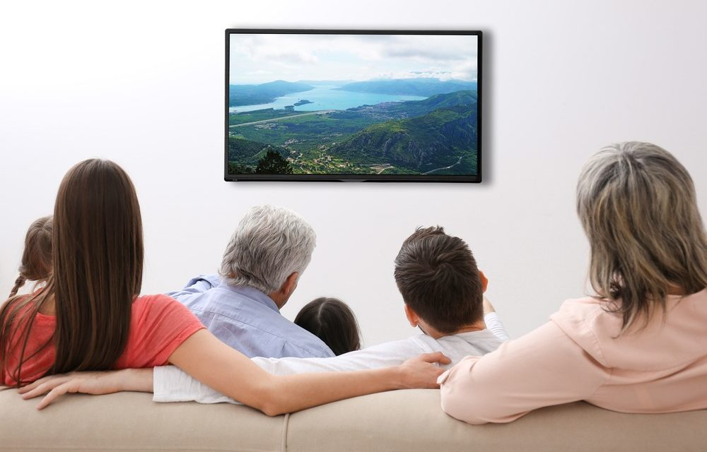 Familie sitzt zu Hause vor dem Fernseher