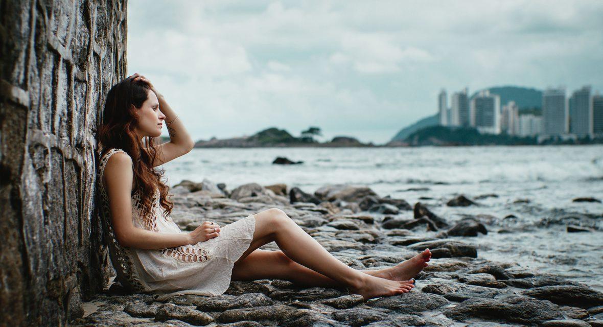 Frau sitzt traurig am Strand und denkt nach.