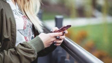 Blonde Frau schreibt auf ihrem Handy