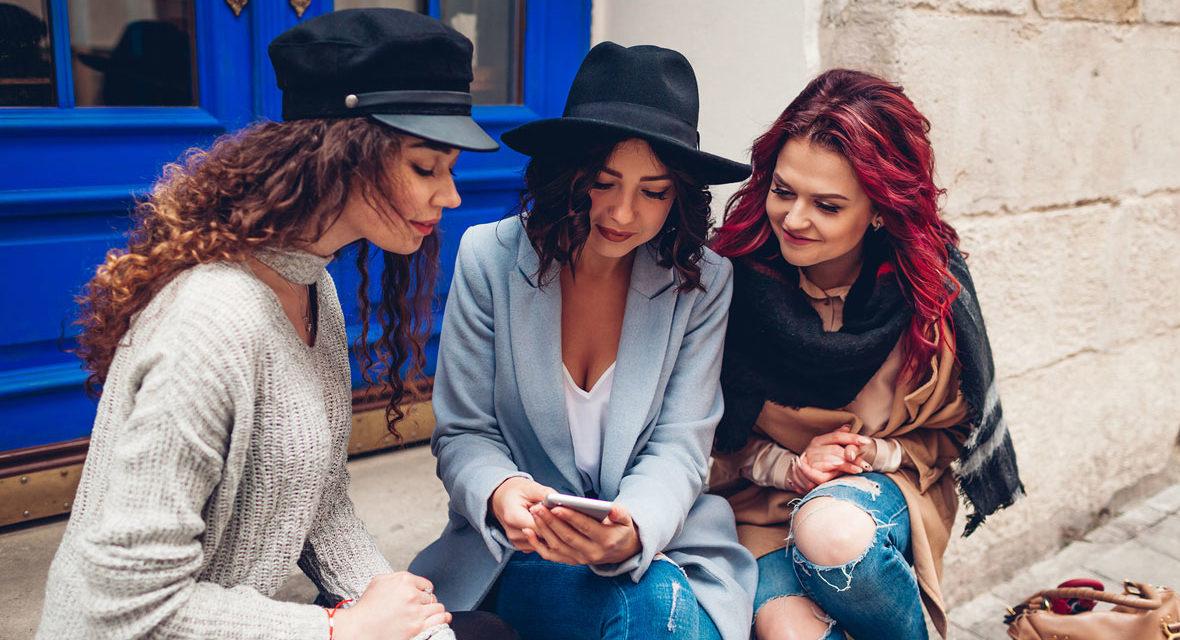 Drei Frauen schauen auf ein Smartphone