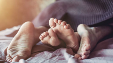 Ein Paar liegt unter einer Bettdecke