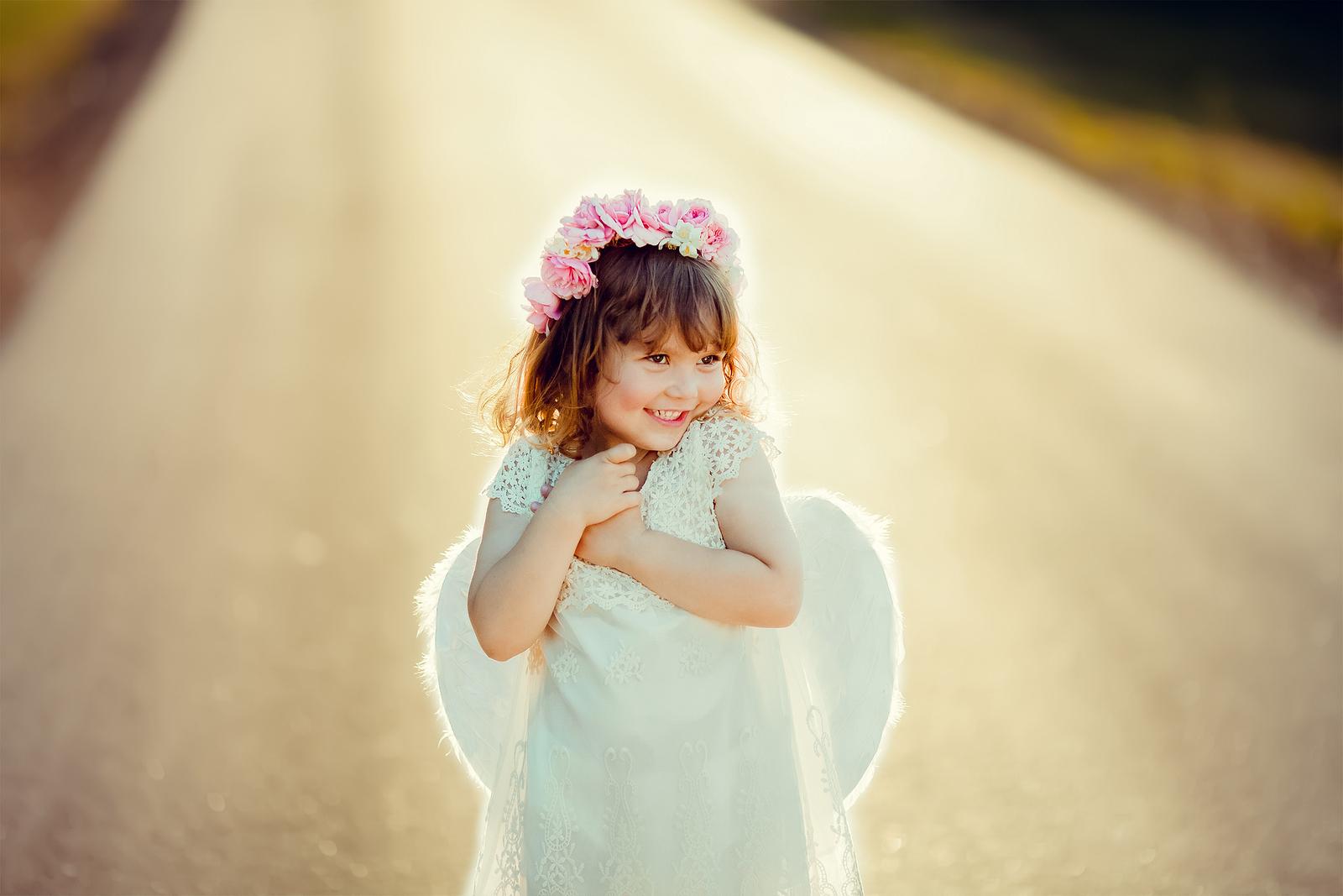 Kleines Mädchen freut sich, weil es Engelsflügel basteln kann und trägt sie stolz