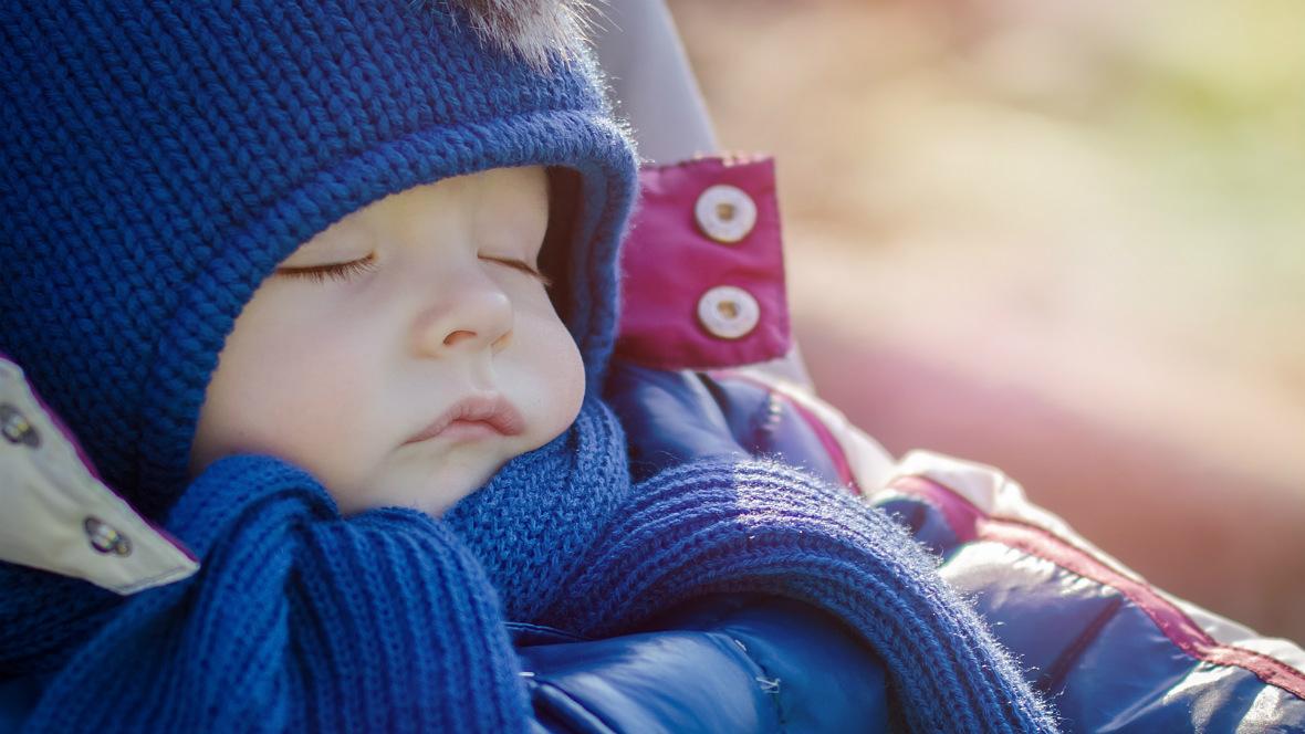 Ein kleines Kind schläft im Kinderwagen