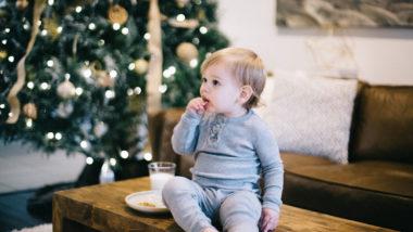 Kind isst Keks an vor Weihnachtsbaum