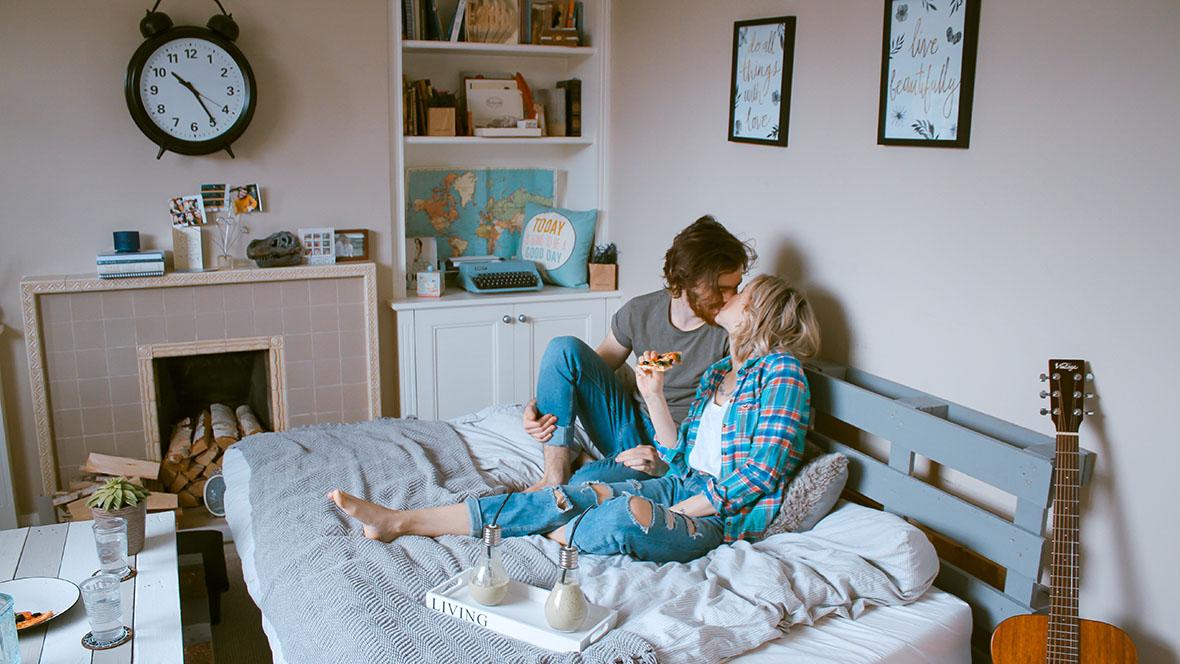 Mit dem Ovulationstest gelingt es vielleicht auch diesem Paar, das verliebt auf dem Bett sitzt und sich küsst, die fruchtbaren Tage und den Eisprung zu bestimmen.
