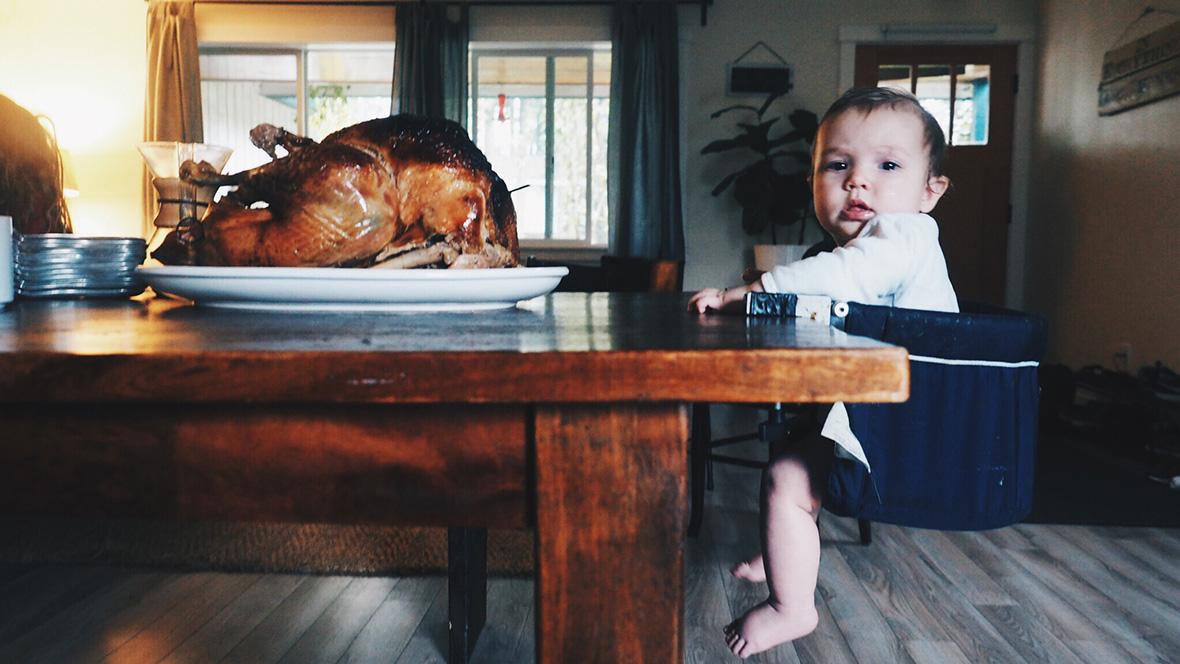 Baby sitzt am Tisch vor einem Truthahn