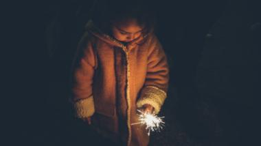 Silvester mit Kind: Mädchen hat eine Wunderkerze