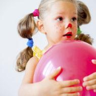 Verkleidetes Mädchen spielt Faschingsspiel mit Luftballon