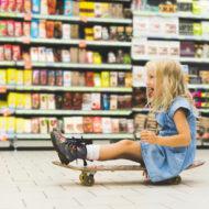 Mädchen fährt trotzig mit Skateboard durch den Supermarkt