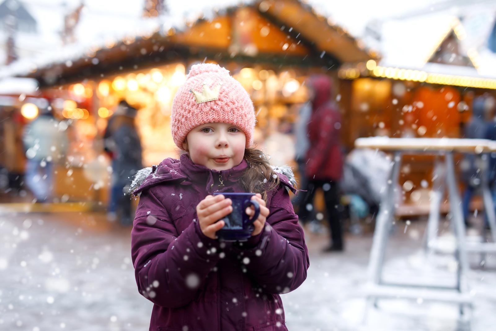 Kleines Mädchen pustet auf einem Weihnachtsmarkt in eine Tasse