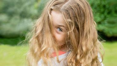 Mädchen mit langen blonden Haaren schaut über ihre Schulter