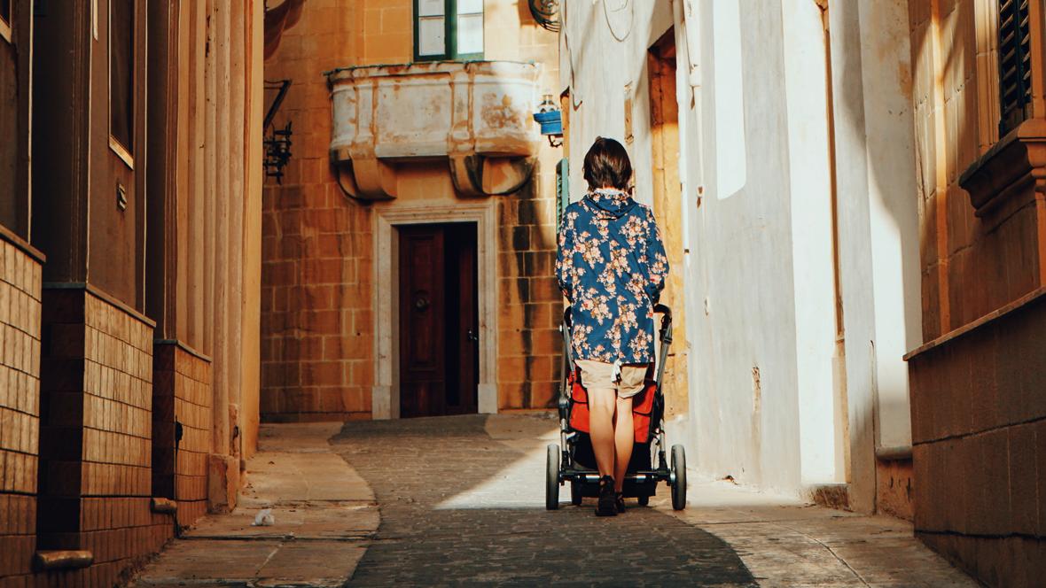 Frau schiebt einen Kinderwagen durch die Straßen