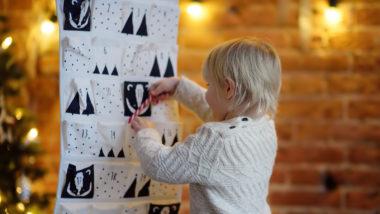 kleiner Junge bestaunt eine Adventskalender Idee und steckt eine Zuckerstange in eine Tasche