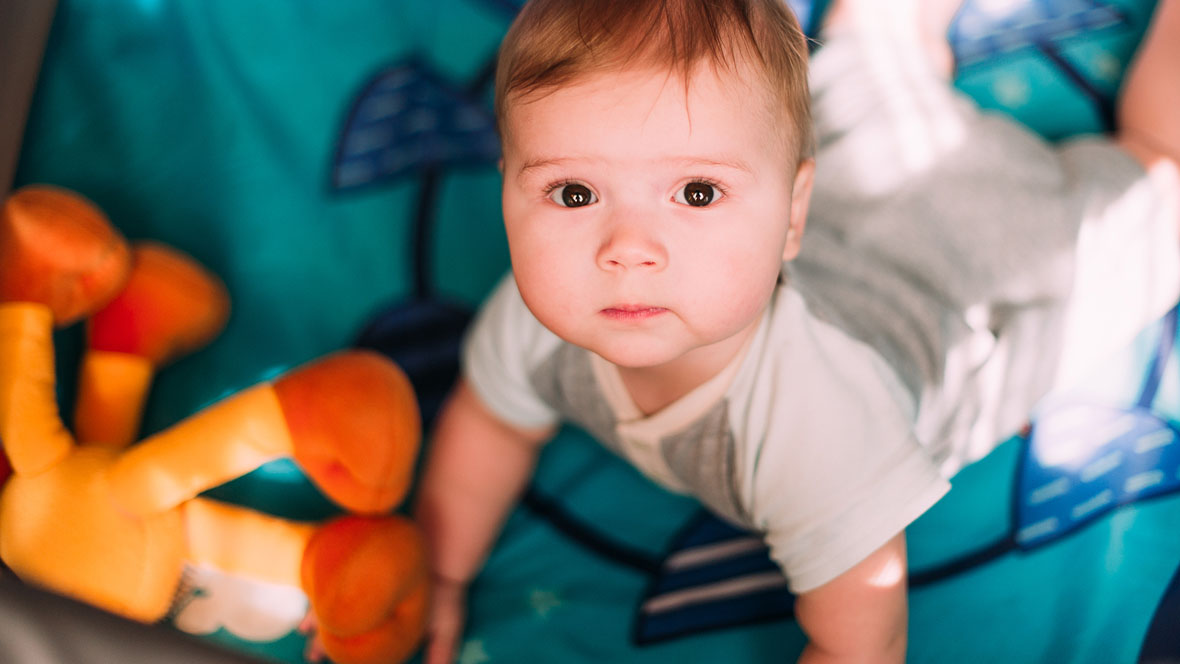 Baby im Laufgitter guckt nach oben