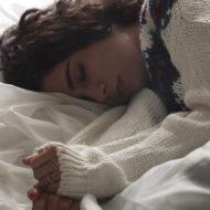 Schwangere liegt mit Übelkeit im Bett