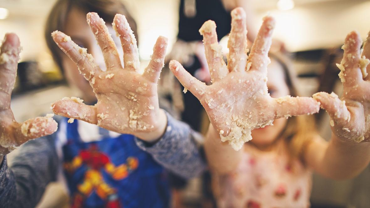 Kinder strecken Hände voll Teig in die Kamera