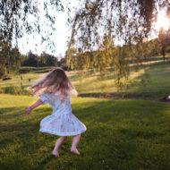 Ein Kleinkind dreht sich auf einer Wiese im Kreis: