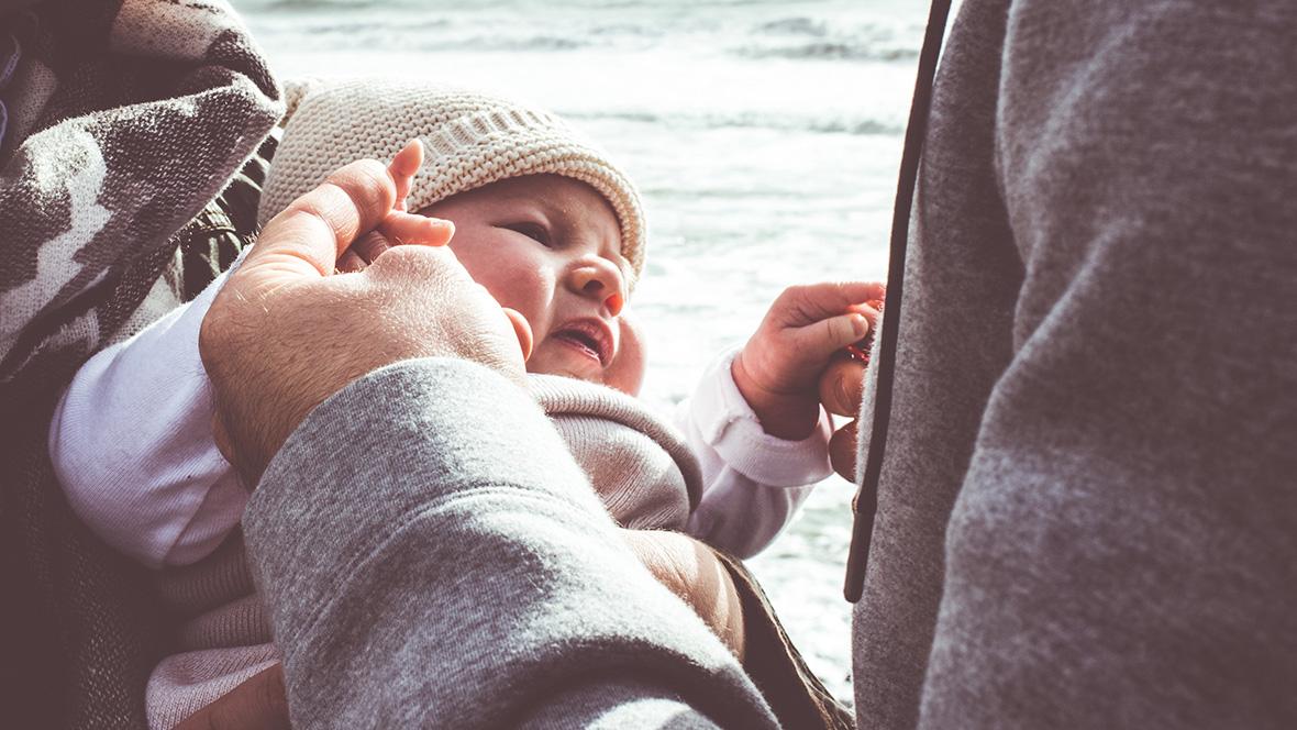Mutter und Vater halten ihr Baby am Strand in den Armen
