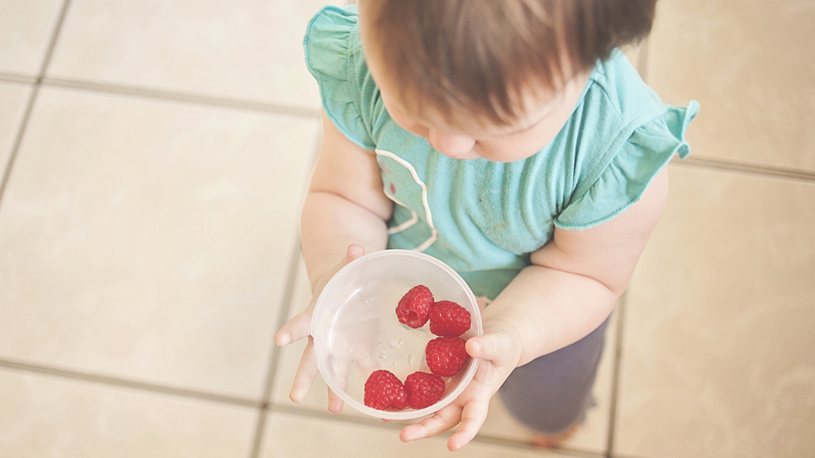 Kind hält eine Schüssel Erdbeeren in der Hand