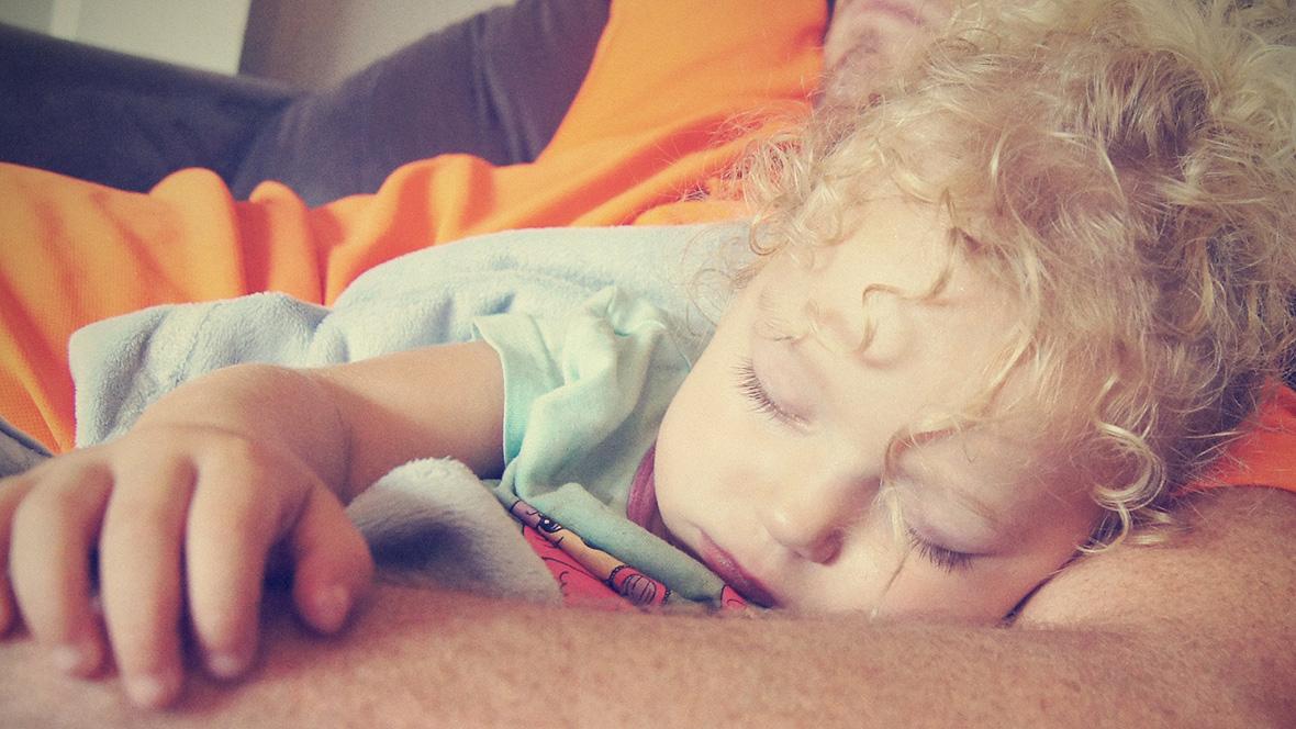 Kleinkind liegt im Bett und schläft