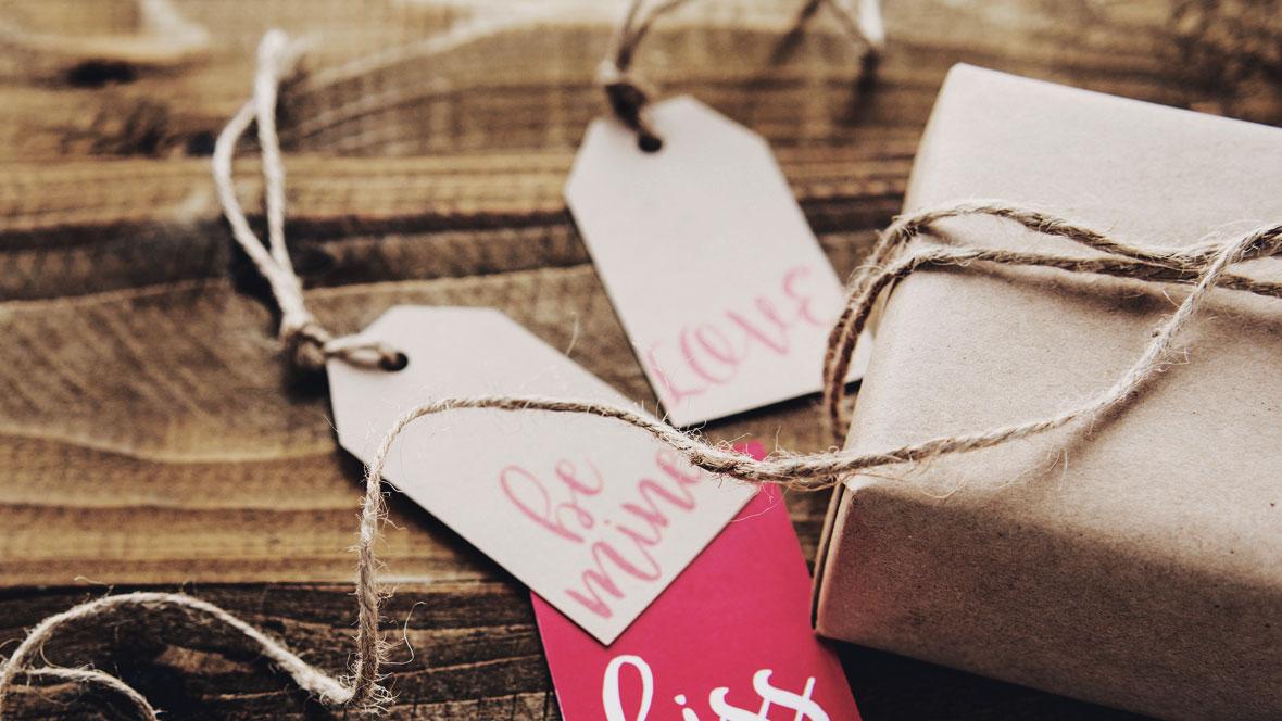 Geschenkanhänger liegen neben einem eingepackten Geschenk
