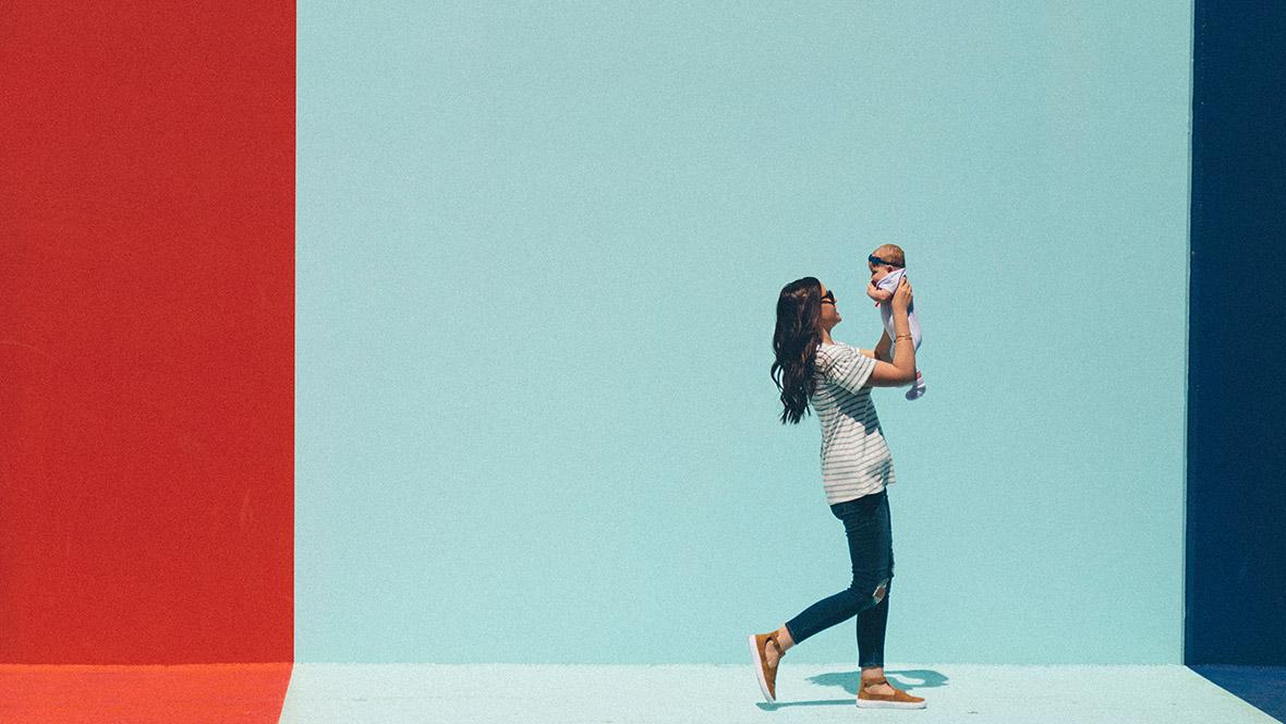 Mutter trägt Baby und hält es weit in die Luft