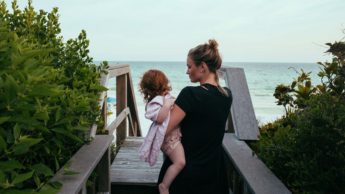 Mutter mit Kind auf dem Arm auf dem Weg zum Meer