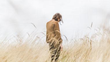 Frau steht allein am Strand