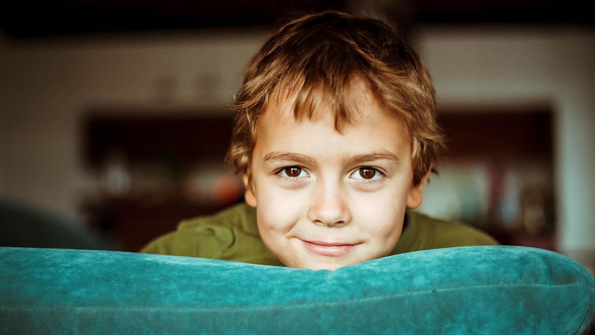 Junge stützt seinen Kopf auf der Sofalehne ab und lächelt in die Kamera