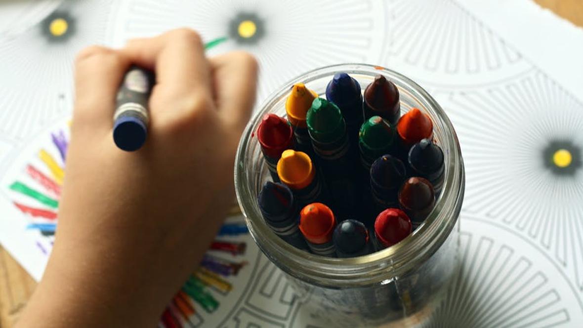 Ein Kind malt ein Bild mit Wachststiften