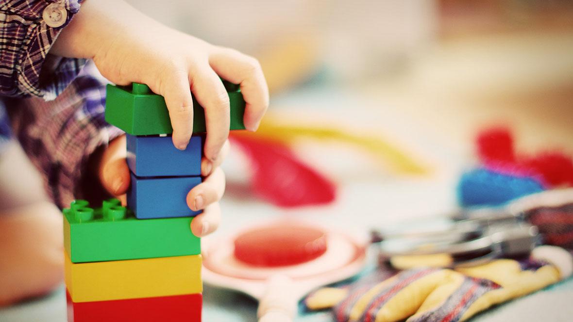 Kind spielt im Kindergarten mit Bausteinen
