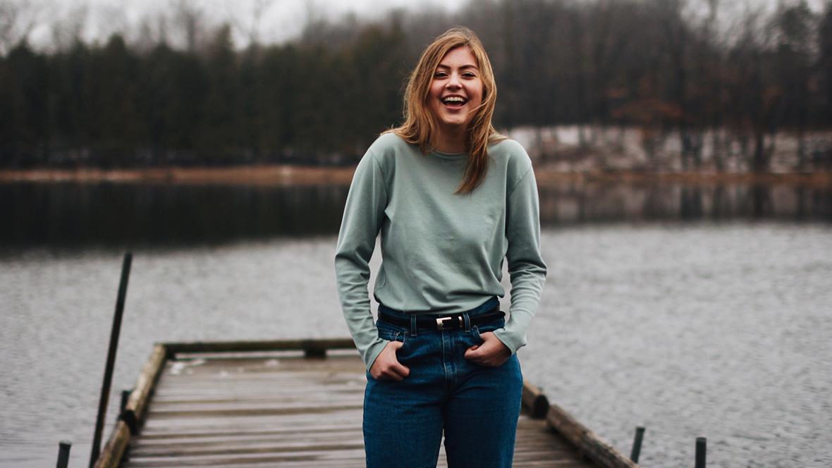 Junge Frau steht auf Steg an einem See und lacht in die Kamera